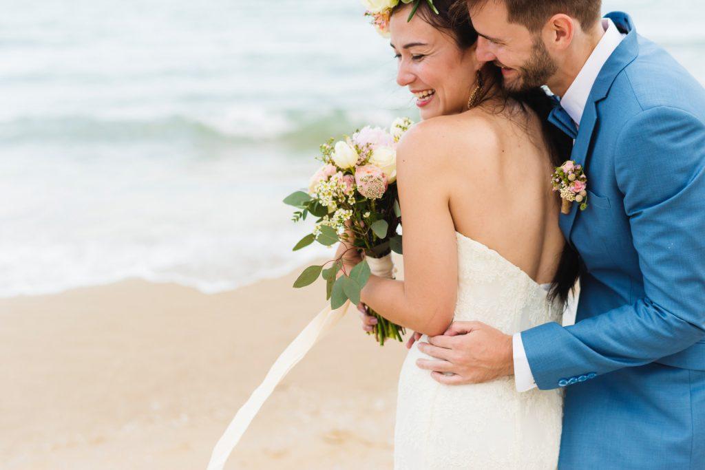 Marido abrazando a su mujer a orillas del mar
