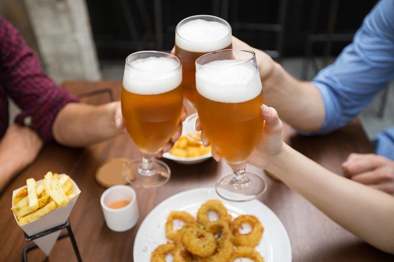 Amigos bebiendo cerveza y comiendo en un bar.